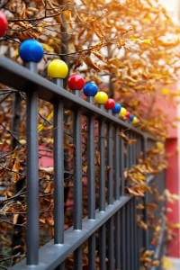 Iron fence with multi colored decorative balls autumn scene